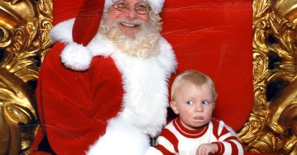 "Baby signs ""Help!"" while sitting on Santa's lap"